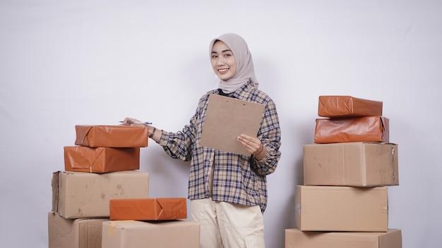 Mooie zakenvrouw die een bestelling voorbereidt die op een witte achtergrond wordt geïsoleerd