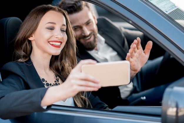 Mooie zakenvrouw die een selfie-portret maakt met een elegante chauffeur die in de auto zit