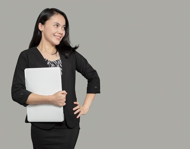 Mooie zakenvrouw die laptop vasthoudt en naar lege ruimte kijkt