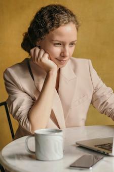 Mooie zakenvrouw die op haar laptop werkt in een café