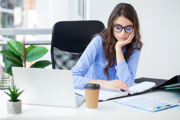 Mooie zakenvrouw die op laptop in heldere, moderne kantoor werkt.