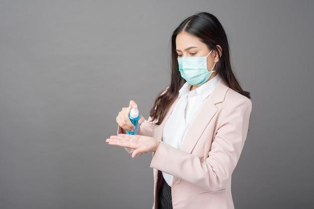 Mooie zakenvrouw gebruikt alcoholspray voor preventie covid- 19