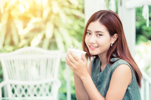 Mooie zakenvrouw hebben genoten in de tuin met koffie.
