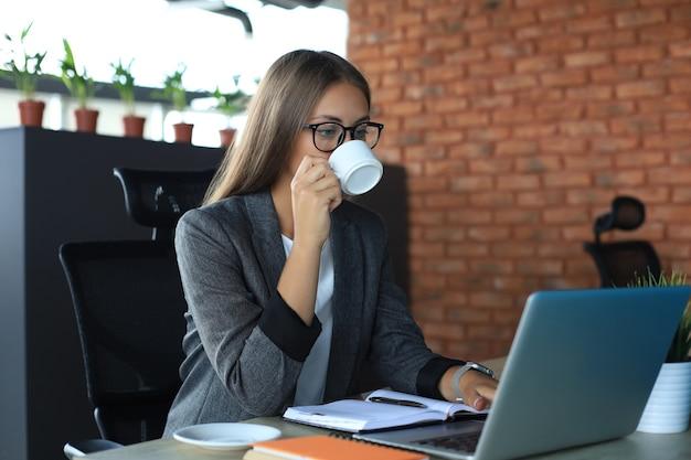 Mooie zakenvrouw houdt koffiekopje en glimlacht terwijl ze op haar werkplek zit.
