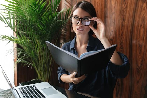 Mooie zakenvrouw in brillen zitten bij de tafel