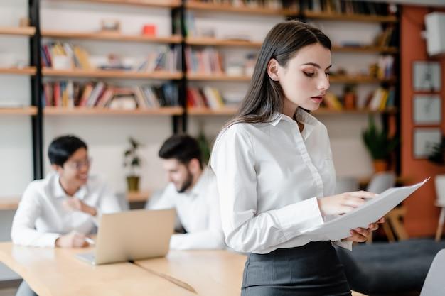 Mooie zakenvrouw in het kantoor met werknemers