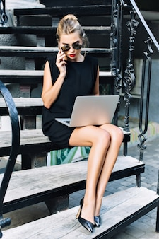 Mooie zakenvrouw in zwarte korte jurk zittend op trappen buiten. ze werkt met een laptop, spreekt aan de telefoon.