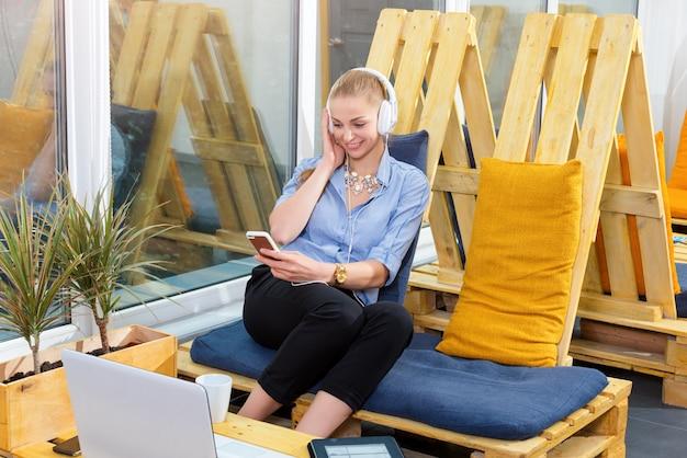 Mooie zakenvrouw luistert naar muziek in moderne loft. freelance werk, chill out en vrije tijd concept. vrouw in businness. freelancer in naaiatelier rust.
