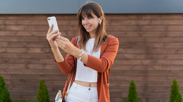 Mooie zakenvrouw met behulp van mobiele telefoon en wandelen in de stad.