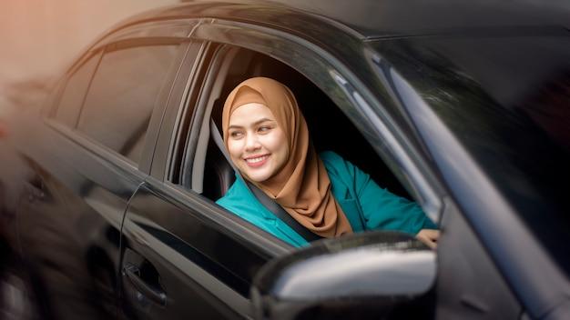 Mooie zakenvrouw met hijab lacht in haar auto