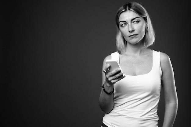 Mooie zakenvrouw met kort haar met behulp van mobiele telefoon