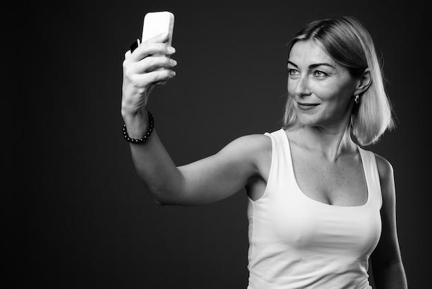 Mooie zakenvrouw met kort haar selfie met telefoon te nemen