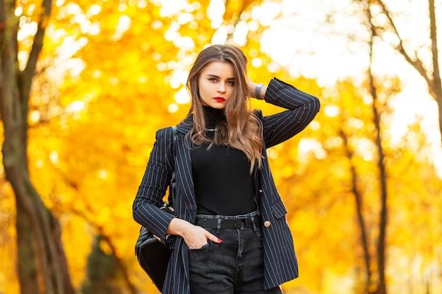 Mooie zakenvrouw met rode lippen in een modieus elegant pak met een blazer, trui en rugzak wandelingen in de natuur met felgekleurde gouden herfstbladeren