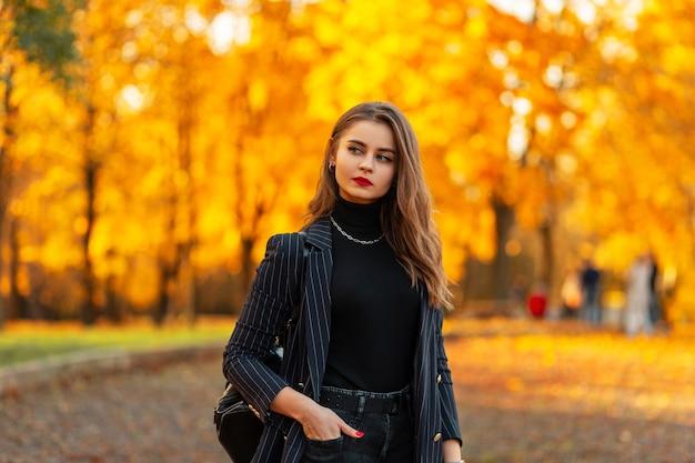 Mooie zakenvrouw met rode lippen in een modieus zwart pak met een jas, trui en rugzak loopt in een herfstpark met felgeel gebladerte. vrouwelijke elegantie stijl en schoonheid