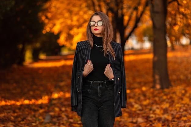 Mooie zakenvrouw met stijlvolle zonnebril in modieuze kleding met een blazer en een trui loopt in een herfstpark met gele herfstbladeren. vrouwelijke elegante stijl en schoonheid