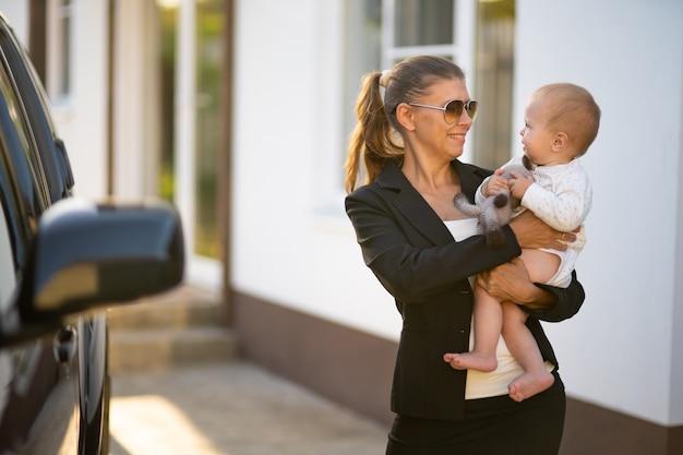 Mooie zakenvrouw moeder in een pak met een klein kind in haar armen tegen de achtergrond van haar huis en een zwarte auto gaat aan het werk