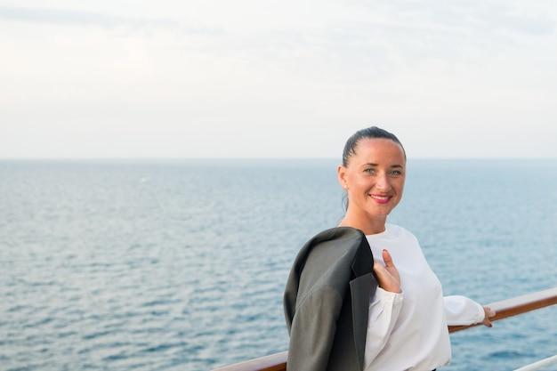 Mooie zakenvrouw of gelukkig schattig meisje met lachend gezicht in witte blouse, grijze jas, heeft rode manicure op het scheepsdek met uitzicht op zee, oceaanwater op bewolkte hemelachtergrond, reizen en toerisme