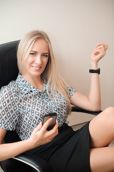 Mooie zakenvrouw ontspannen in haar kantoor.
