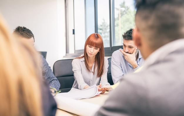 Mooie zakenvrouw op het werk - mensen uit het bedrijfsleven met bestuursvergadering in een modern kantoor - team van managers brainstormen in een startup