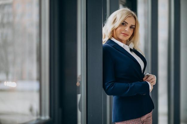 Mooie zakenvrouw op kantoor bij het raam