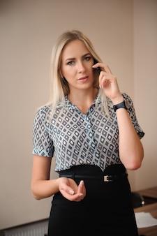 Mooie zakenvrouw praten op mobiele telefoon. het jonge vrouwelijke modelwerk met verkoop in bureau.