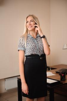 Mooie zakenvrouw praten op mobiele telefoon. het jonge vrouwelijke modelwerk met verkoop in helder bureau.