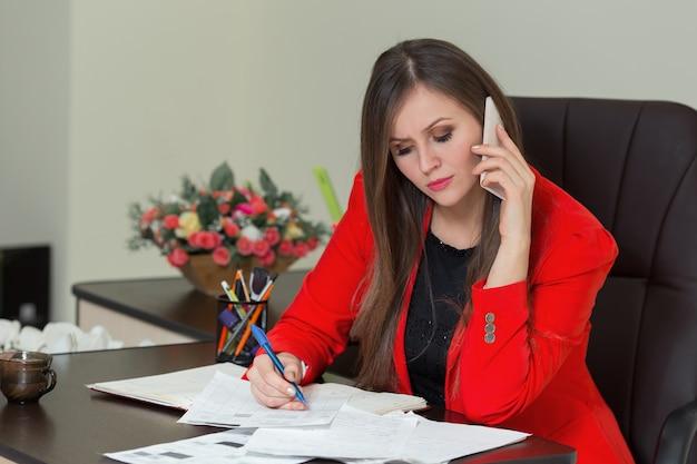 Mooie zakenvrouw praten over de telefoon en schrijven op papier in kantoor.