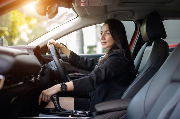 Mooie zakenvrouw rijdende auto bij zonsondergang