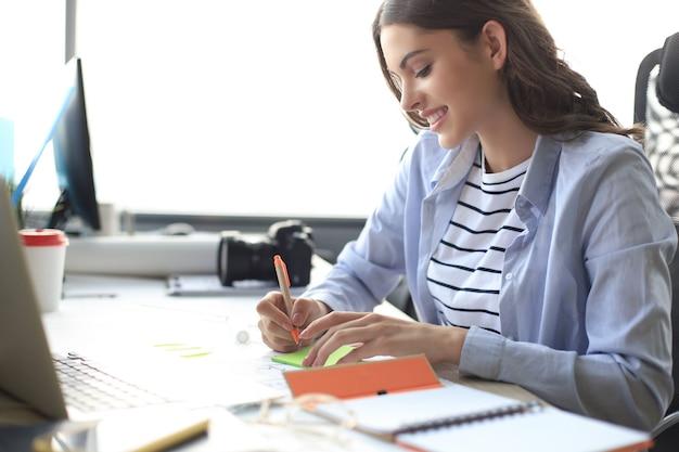 Mooie zakenvrouw schrijft iets op terwijl ze op het bureau zit.