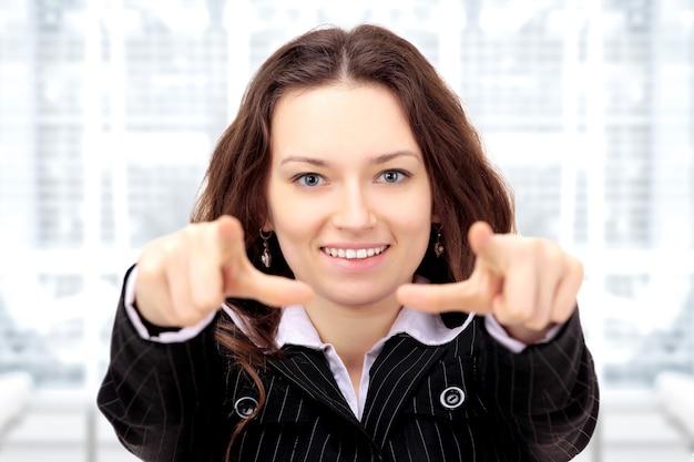 Mooie zakenvrouw toont een voorwaartse wijsvinger op kantoor.