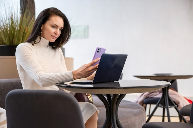 Mooie zakenvrouw typen aan de telefoon zittend aan tafel met laptop.