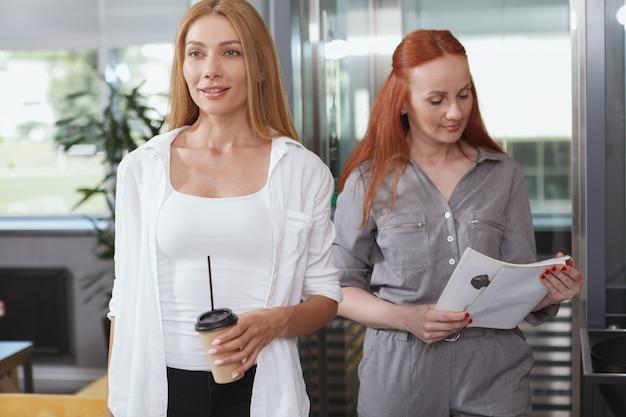 Mooie zakenvrouw verlaten lift met haar collega achter