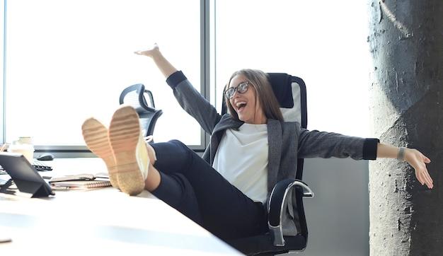 Mooie zakenvrouw viert triomf in zakelijke deal op kantoor met handen omhoog. zakelijke dame is ontspannen op kantoor.