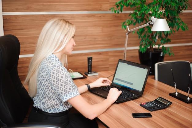 Mooie zakenvrouw werken met verkoop in haar kantoor.