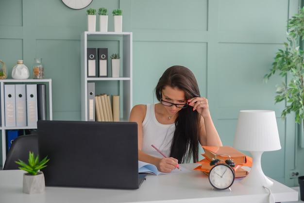 Mooie zakenvrouw werkt op kantoor op een laptop freelancer op het werk geeft de leraar les