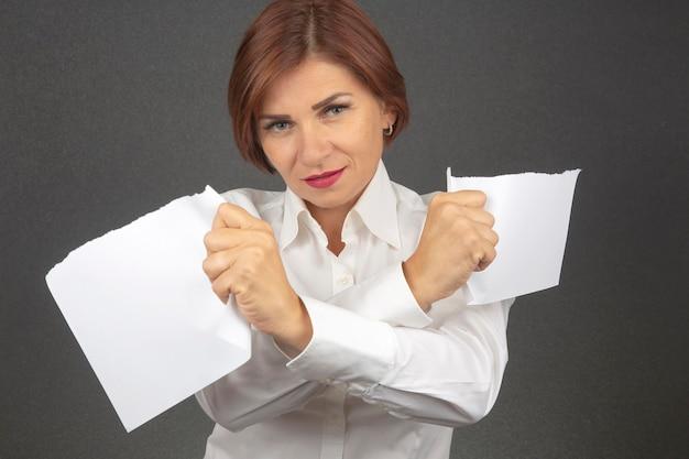 Mooie zakenvrouw witboek doormidden scheuren