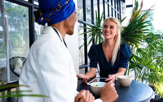 Mooie zakenvrouwen die een pauze nemen in een café om te lunchen