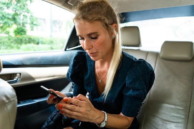 Mooie zakenvrouwen rijden naar de luchthaven en vertrekken voor een werkreis. smartphone gebruiken om te bellen