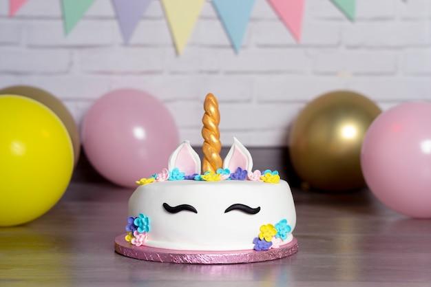 Mooie zelfgemaakte cake in de vorm van een eenhoorn met crèmekleurige bloemen omringd door ballonnen en slingers