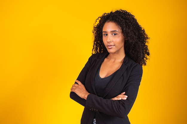 Mooie zelfverzekerde vrouw, gekleed in een power suit, vriendelijke persoonlijkheid, glimlachend geïsoleerd op gele achtergrond.