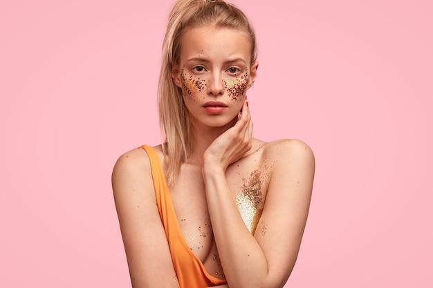 Mooie zelfverzekerde vrouw heeft feestelijke make-up, ziet er serieus uit, bereidt zich voor op een feestje met vrienden, heeft blote schouders,
