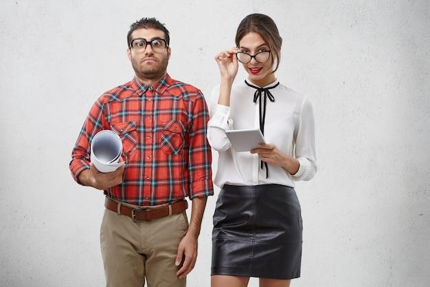 Mooie zelfverzekerde vrouw kijkt door stijlvolle brillen, houdt tabletcomputer