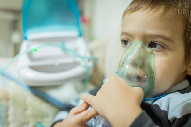 Mooie zieke jongen inhalatie therapie door het masker van inhalator.