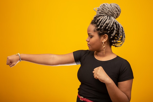 Mooie zij jonge afrikaanse amerikaanse vrouw met het haar van het vreeshaar stellende stempels in de lucht