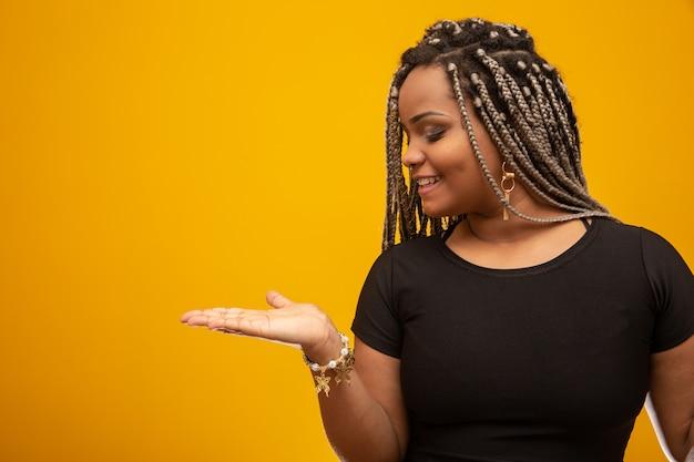 Mooie zij jonge afrikaanse amerikaanse vrouw met ontzettingshaar die de palm van de hand tonen