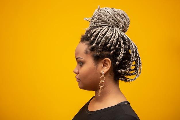 Mooie zij jonge afrikaanse amerikaanse vrouw met ontzettingshaar op geel