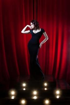 Mooie zingende vrouw op het podium op rood gordijn