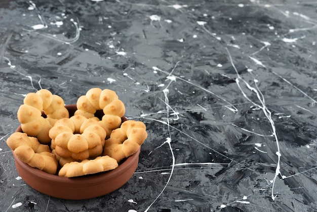 Mooie zoete koekjes voor thee in een kom van klei op een marmeren ondergrond