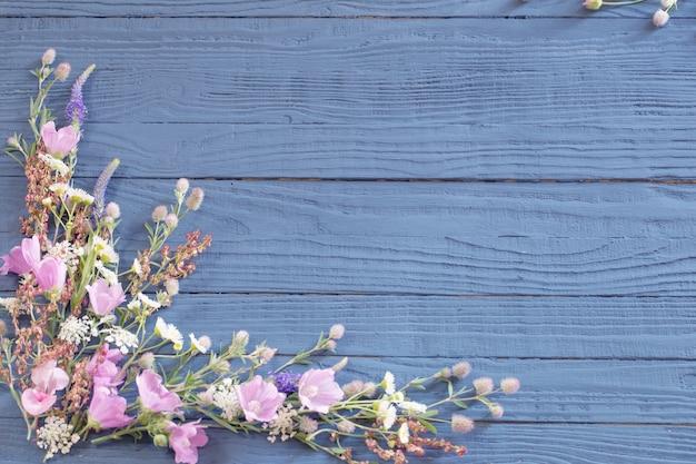 Mooie zomerbloemen op donkerblauwe houten achtergrond