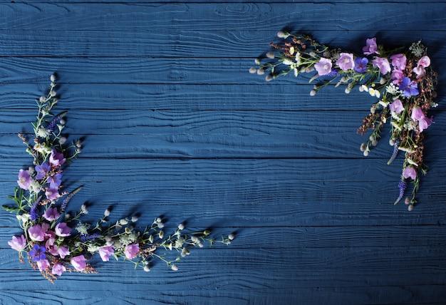 Mooie zomerbloemen op donkerblauwe houten muur